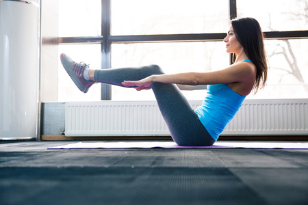 Photo for Happy young woman doing exercise on yoga mat at gym - Royalty Free Image