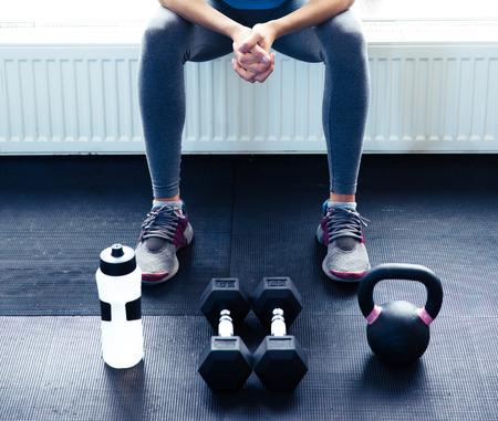 Foto de Closeup image of a woman sitting at gym with dumbbells, shaker and weight - Imagen libre de derechos