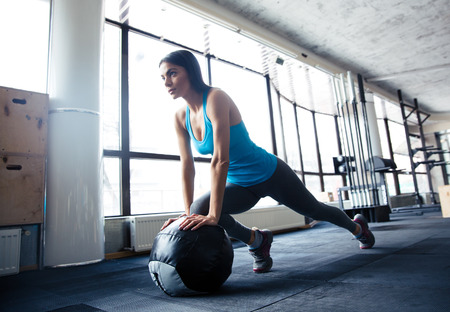 Photo for Young woman doing exercise with fit ball at gym - Royalty Free Image