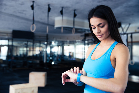 Foto de Happy young woman using activity tracker in fitness gym - Imagen libre de derechos
