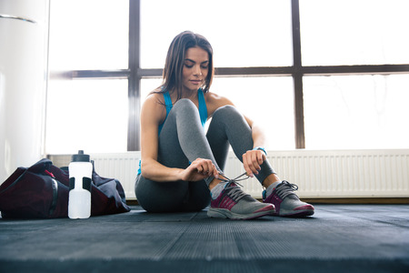Photo for Beautiful woman tying shoelaces at gym - Royalty Free Image