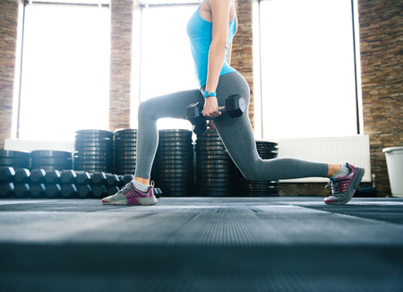 Photo for Closeup image of a woman working out with dumbbells at gym - Royalty Free Image
