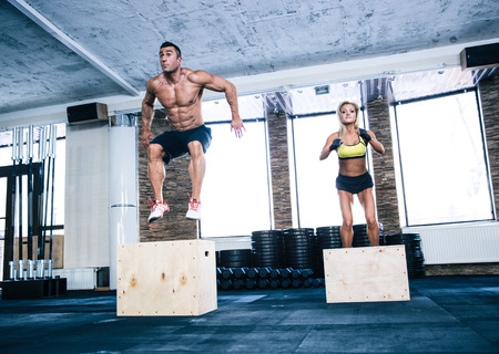 Photo for Group of man and woman jumping on fit box at gym - Royalty Free Image