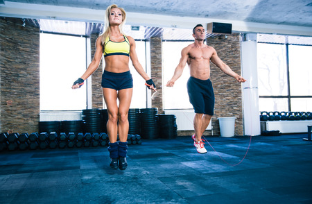 Handsome muscular man and beautiful sporty woman workout with jumping rope in crossfit gym