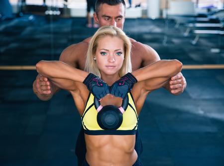 Foto de Woman workout with kettle ball and coach in gym - Imagen libre de derechos