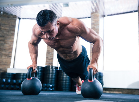 Foto de Handsome muscular man doing push ups on kettle ball in crossfit gym - Imagen libre de derechos