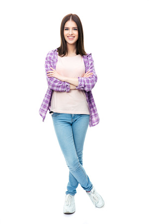 Photo pour Full length portrait of a smiling cute female student standing over white background with arms folded and looking at camera - image libre de droit