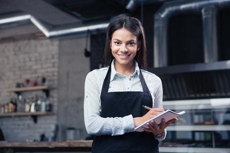 Foto de Happy charming female waiter in apron writing order and looking at camera - Imagen libre de derechos