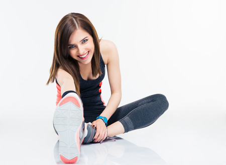 Foto de Happy fitness woman doing stretching exercises isolated on a white background. Looking at camera - Imagen libre de derechos