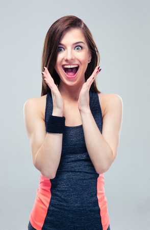 Foto de Amazed happy fitness woman on gray background. Looking at camera - Imagen libre de derechos