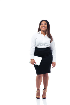 Full length portrait of a smiling afro american businesswoman holding tablet computer over whiet background. Looking at camera