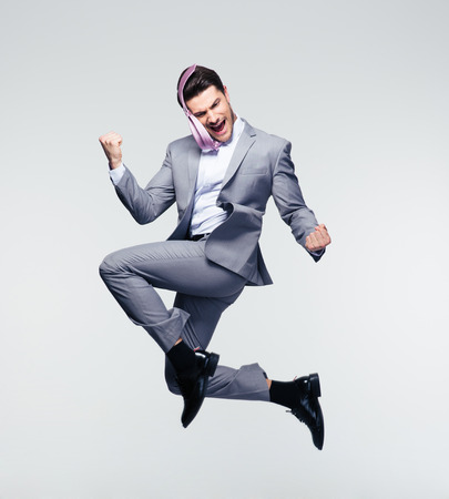 Foto de Happy businessman jumping in air over gray background - Imagen libre de derechos
