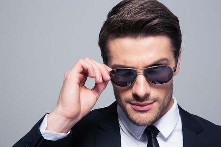 Photo pour Portrait of a fashion businessman in sunglasses looking at camera over gray background - image libre de droit