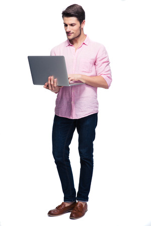 Photo for Young man standing and using laptop isolataed on a white background - Royalty Free Image