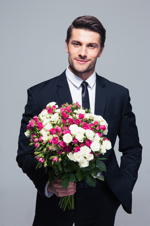 Photo pour Handsome businessman holding flowers over gray background and looking at camera - image libre de droit