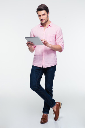 Photo pour Full length portrait of a young man using tablet computer over gray background and looking at camera - image libre de droit