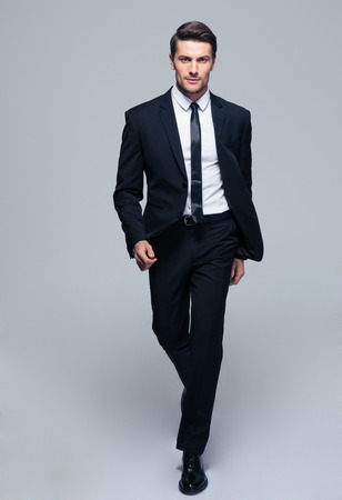Photo for Full length portrait of a fashion male model over gray background. Looking at camera - Royalty Free Image