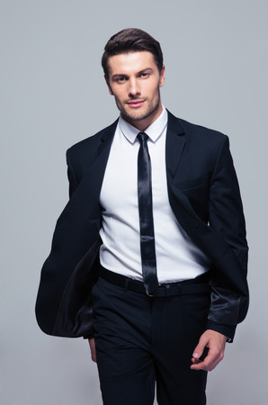 Photo pour Fashion young businessman over gray background. Looking at camera - image libre de droit