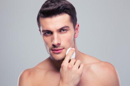 Foto de Man cleaning face skin with batting cotton pads over gray background - Imagen libre de derechos