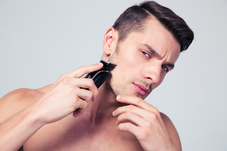 Photo for Handsome young man shaving with electric razor over gray background and looking at camera - Royalty Free Image
