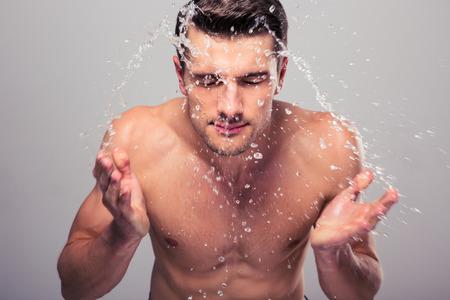 Foto de Young man spraying water on his face over gray background - Imagen libre de derechos