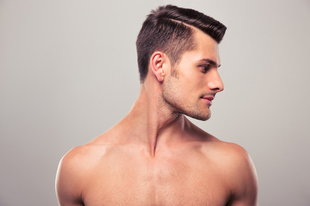 Photo for Handsome young man looking away over gray background - Royalty Free Image