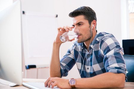 Photo pour Handsome businessman in casual cloth using PC and drinking water in office - image libre de droit