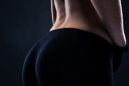 Photo for Closeup portrait of a fitness female buttocks over black background - Royalty Free Image