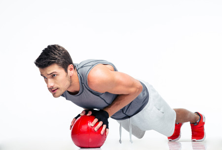 Foto de Sports man working out with fitness ball isolated on a white background - Imagen libre de derechos