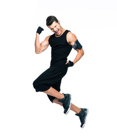 Foto de Full length portrait of a cheerful fitness man jumping isolated on a white background - Imagen libre de derechos