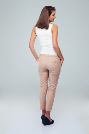 Foto de Back view portrait of a casual woman standing over gray background - Imagen libre de derechos