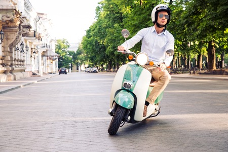 Foto de Fashion man driving a scooter in helmet in old town - Imagen libre de derechos