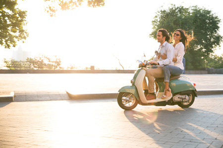 Photo pour Happy young couple riding a scooter and having fun. Sun is shining in the morning - image libre de droit