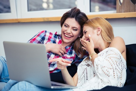 Foto de Two laughing girls sitting on sofa and watching movie on laptop - Imagen libre de derechos
