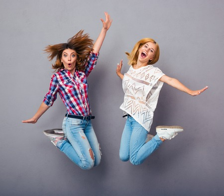 Foto de Two cheerful girls jumping over gray background - Imagen libre de derechos