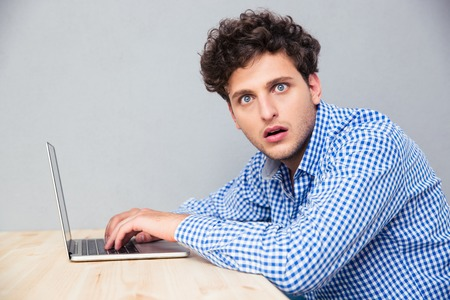 Photo for Side view portrait of a shocked man sitting at the table with laptop and looking at camera - Royalty Free Image