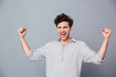 Photo for Successful young man celebrating his winning over gray background. Looking at camera - Royalty Free Image