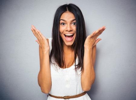 Foto de Portrait of a happy amazed woman over gray background. Looking at camera - Imagen libre de derechos