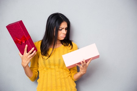 Foto de Unhappy young woman holding gift box over gray background - Imagen libre de derechos