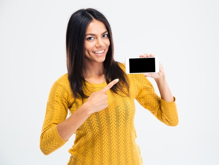 Photo pour Cheerful cute woman pointing finger on smartphone screen isolated on a white background. Looking at camera - image libre de droit