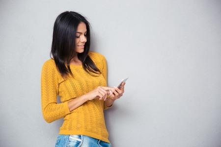 Foto de Happy casual woman using smartphone over gray background - Imagen libre de derechos