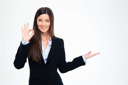 Foto de Happy businesswoman showing ok sign and holding copyspace on the palm isolated on a white background. Looking at camera - Imagen libre de derechos