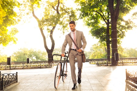 Photo pour Confident young businessman walking with bicycle on the street in town - image libre de droit