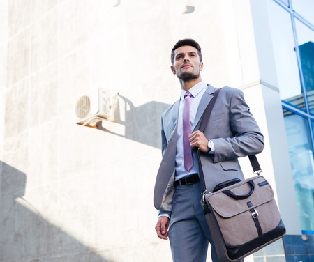 Foto de Portrait of a handsome businessman standing outdoors near office building - Imagen libre de derechos