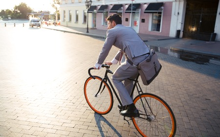 Photo pour Businessman riding bicycle to work on urban street in morning - image libre de droit