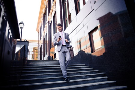 Photo pour Happy businessman walking on the stairs and using smartphone outdoors - image libre de droit