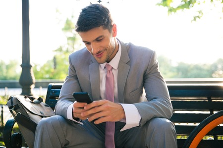 Photo for Happy businessman sitting on the bench outdoors and using smartphone - Royalty Free Image