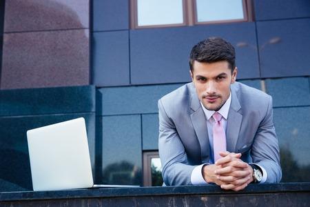 Foto de Portrait of a confident businessman with laptop computer outdoors. Looking at camera - Imagen libre de derechos