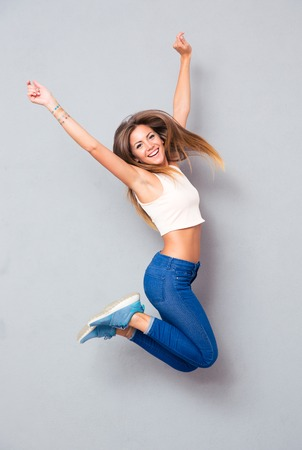 Laughing young girl jumping over gray background. Looking at camera