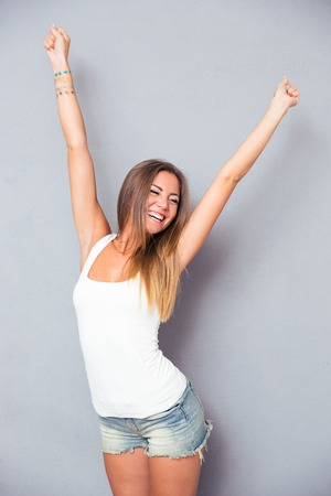 Foto de Cheerful young woman posing over gray background - Imagen libre de derechos